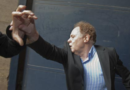 Alan Rosenberg of the Church of Scientology Paris, pushes back reporters as he leaves court. Photo: Reuters